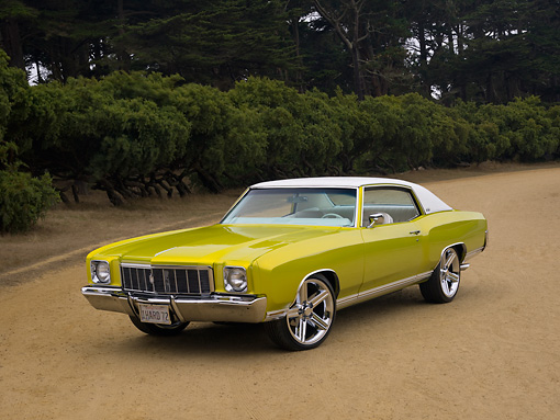 AUT 23 RK1128 01 © Kimball Stock 1972 Chevrolet Monte Carlo Candy Lime Gold 3/4 Front View On Dirt Trees Background