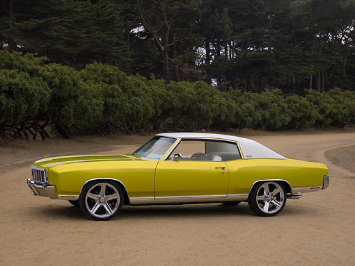AUT 23 RK1129 01 © Kimball Stock 1972 Chevrolet Monte Carlo Candy Lime Gold 3/4 Side View On Dirt Trees Background