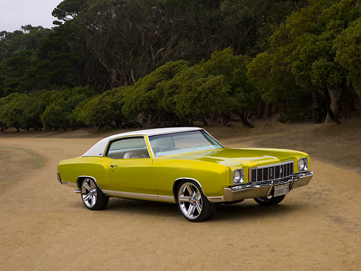 AUT 23 RK1130 01 © Kimball Stock 1972 Chevrolet Monte Carlo Candy Lime Gold 3/4 Front View On Dirt Trees Background