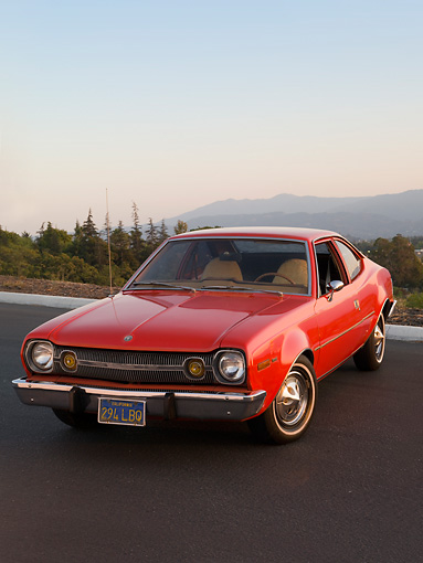 AUT 23 RK1579 01 © Kimball Stock 1974 AMC Hornet Hatchback Red 3/4 Front View On Pavement By Mountains Trees