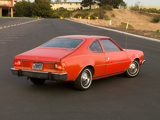AUT 23 RK1580 01 © Kimball Stock 1974 AMC Hornet Hatchback Red 3/4 Rear View On Pavement By Buildings Trees Dirt