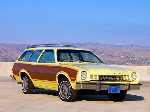 AUT 23 RK1595 01 © Kimball Stock 1977 Ford Pinto Wagon Chartreuse With Woodgrain Side Paneling 3/4 Front View On Pavement By Hills Sky