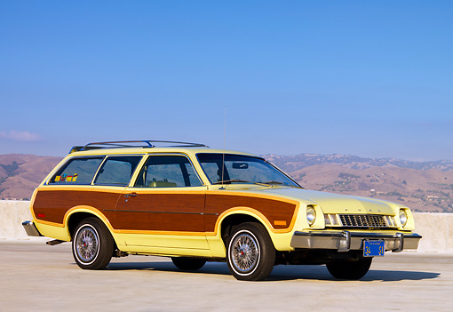 AUT 23 RK1597 01 © Kimball Stock 1977 Ford Pinto Wagon Chartreuse With Woodgrain Side Paneling 3/4 Front View On Pavement By Hills Sky
