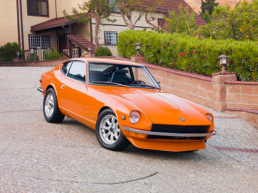 AUT 23 RK1654 01 © Kimball Stock 1973 Datsun 240Z Orange 3/4 Front View On Driveway By House