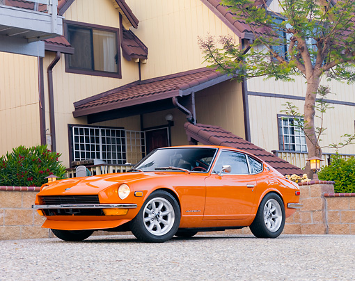 AUT 23 RK1656 01 © Kimball Stock 1973 Datsun 240Z Orange 3/4 Front View On Driveway By House