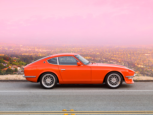 AUT 23 RK1660 01 © Kimball Stock 1972 Datsun 240Z Orange Profile View On Road Overlooking City Lights