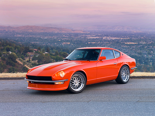 AUT 23 RK1663 01 © Kimball Stock 1972 Datsun 240Z Orange 3/4 Front View On Road Overlooking Valley