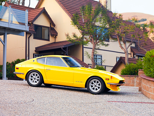 AUT 23 RK1672 01 © Kimball Stock 1973 Datsun 240Z Yellow 3/4 Front View On Driveway By House