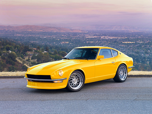 AUT 23 RK1673 01 © Kimball Stock 1972 Datsun 240Z Yellow 3/4 Front View On Road Overlooking Valley