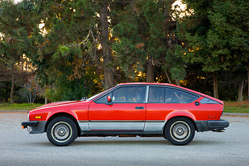 AUT 23 RK1735 01 © Kimball Stock 1981 Alfa Romeo GTV6 Coupe Red Profile View On Pavement By Trees