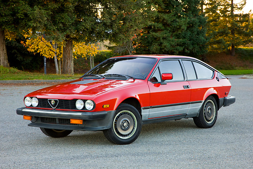 AUT 23 RK1736 01 © Kimball Stock 1981 Alfa Romeo GTV6 Coupe Red 3/4 Front View On Pavement By Trees