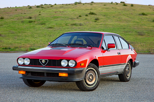 AUT 23 RK1740 01 © Kimball Stock 1981 Alfa Romeo GTV6 Coupe Red 3/4 Front View On Pavement By Hills