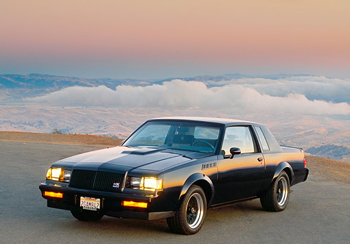 AUT 24 RK0059 02 © Kimball Stock 1987 Buick GNX Black 3/4 Front View On Pavement Sunset Background