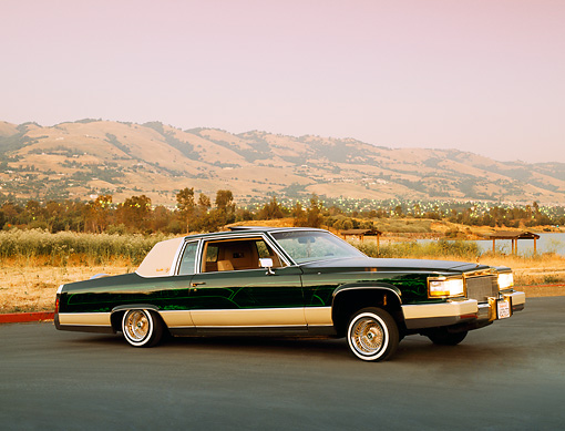 AUT 24 RK0116 01 © Kimball Stock 1984 Cadillac Coupe Deville Lowrider Green 3/4 Side View On Pavement Mountains Filtered