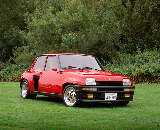 AUT 24 RK0133 03 © Kimball Stock 1985 Renault 5 Turbo 2 Red Low 3/4 Front View On Grass Trees Background