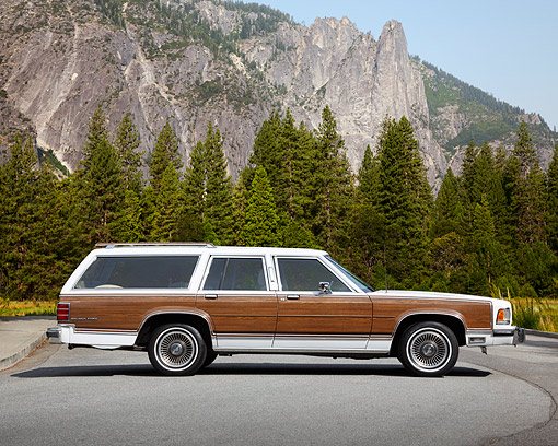 AUT 24 RK0165 01 © Kimball Stock 1988 Mercury Marquis Colony Park White With Wood Panel Profile View On Pavement By Mountains