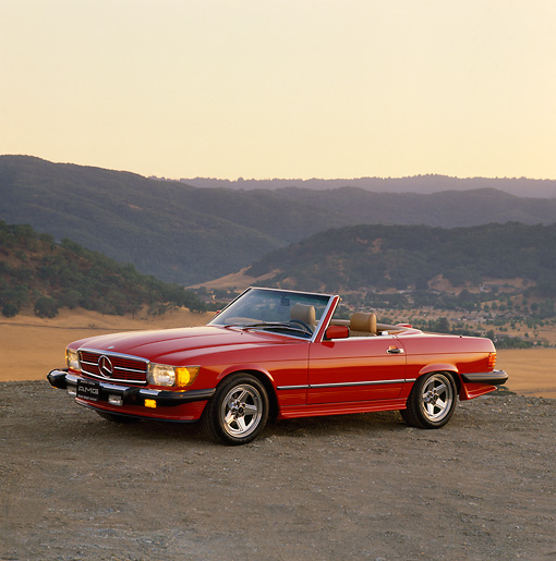 AUT 24 RK0008 03 © Kimball Stock 1987 Mercedes-Benz Convertible Red 3/4 Side View On Dirt Hills Background