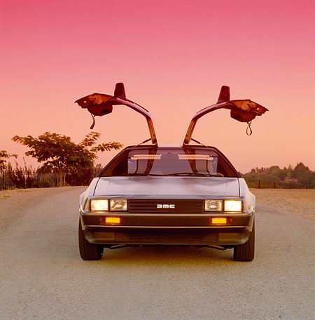 AUT 24 RK0016 01 © Kimball Stock 1980's Delorean Silver Head On Doors Open On Pavement Pink Sky