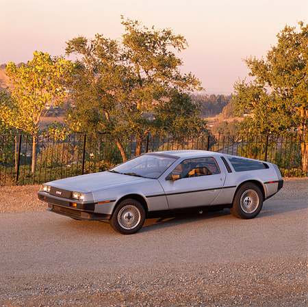 AUT 24 RK0025 01 © Kimball Stock 1980's Delorean Silver 3/4 Side View On Pavement Trees Background