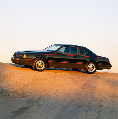 AUT 24 RK0051 01 © Kimball Stock 1986 Ford Thunderbird Turbo Coupe Black 3/4 Front View On Pavement Hill At Dusk