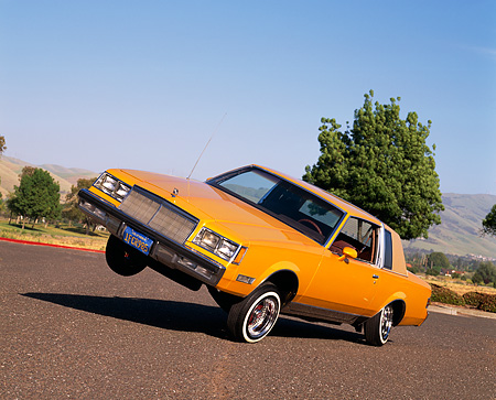 AUT 24 RK0097 09 © Kimball Stock 1982 Buick Regal Lowrider Orange With Hydrolics 3/4 Front View On Pavement By Trees Blue Sky