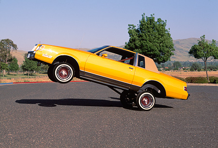 AUT 24 RK0105 08 © Kimball Stock 1982 Buick Regal Lowrider Orange 3/4 Front View On Pavement Trees Blue Sky