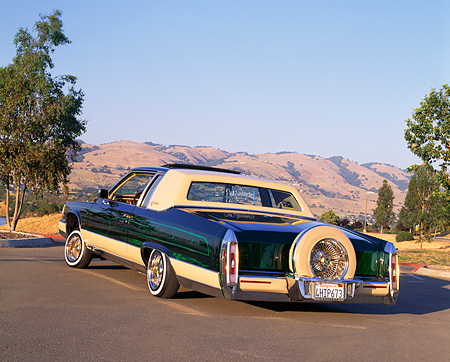 AUT 24 RK0113 01 © Kimball Stock 1984 Cadillac Coupe Deville Lowrider Green 3/4 Rear View On Pavement Trees Mountains