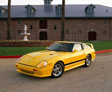 AUT 24 RK0146 04 © Kimball Stock 1982 Nissan 280ZX Full Custom Yellow 3/4 Front View On Gravel By Grass And Brick Building