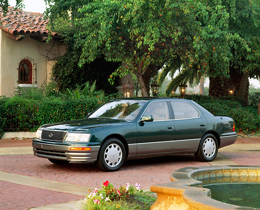 AUT 25 RK0043 02 © Kimball Stock 1996 Lexus LS400 Green 3/4 Side View On Brick Driveway And Trees