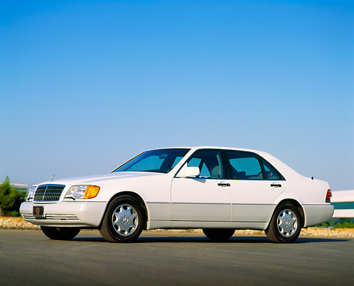 AUT 25 RK0209 01 © Kimball Stock 1992 Mercedes-Benz Sedan White Low 3/4 Side View On Pavement Blue Sky