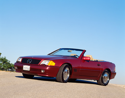 AUT 25 RK0223 02 © Kimball Stock 1991 Mercedes Benz 500SL Convertible Burgundy 3/4 Side On Pavement Hill Blue Sky
