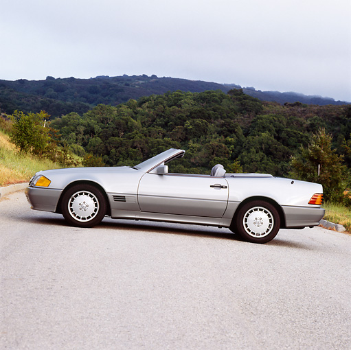 AUT 25 RK0232 01 © Kimball Stock 1990 Mercedes-Benz 500SL Convertible Silver Profile View On Pavement Trees In Background Overcast