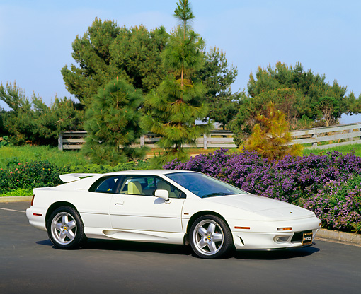 AUT 25 RK0410 03 © Kimball Stock 1995 Lotus Esprit S4 White Side 3/4 View On Pavement By Trees
