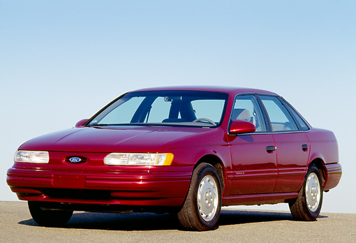 AUT 25 RK0495 02 © Kimball Stock 1993 Ford Taurus Burgundy Side 3/4 View On Pavement Hill Blue Sky
