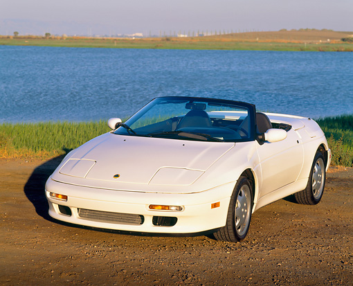 AUT 25 RK0524 03 © Kimball Stock 1991 Lotus Elan Convertible White 3/4 Front View On Dirt By Water