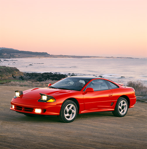AUT 25 RK0595 02 © Kimball Stock 1991 Dodge Stealth Red 3/4 Front View On Sand By Ocean Filtered