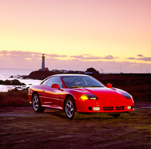 AUT 25 RK0596 02 © Kimball Stock 1991 Dodge Stealth Red 3/4 Front View On Sand By Ocean At Dusk