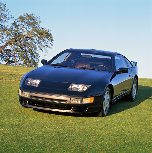 AUT 25 RK0792 05 © Kimball Stock 1990 Nissan 300ZX Turbo Black 3/4 Front View On Grass Hill Blue Sky