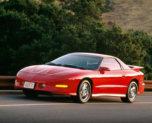 AUT 25 RK0842 11 © Kimball Stock 1993 Pontiac Firebird Trans Am Red 3/4 Front View On Road By Bushes
