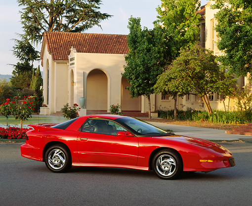 AUT 25 RK0847 02 © Kimball Stock 1993 Pontiac Firebird Trans Am Red 3/4 Side View On Pavement By Building And Trees