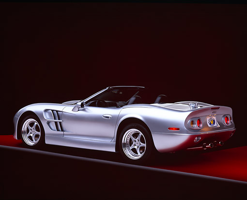 AUT 25 RK1126 06 © Kimball Stock 1999 Shelby Series 1 Convertible Silver 3/4 Rear View On Red Floor Gray Line Studio