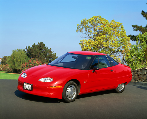 AUT 25 RK1172 03 © Kimball Stock 1999 General Motors EV1 Electric Car Red 3/4 Front View On Pavement Trees Blue Sky