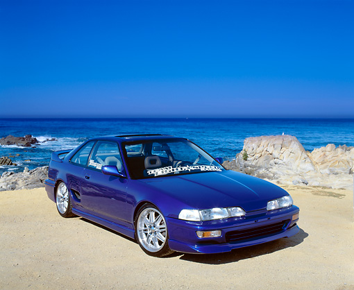 AUT 25 RK1246 03 © Kimball Stock 1991 Acura Integra Custom Blue 3/4 Front View On Sand By Ocean Blue Sky
