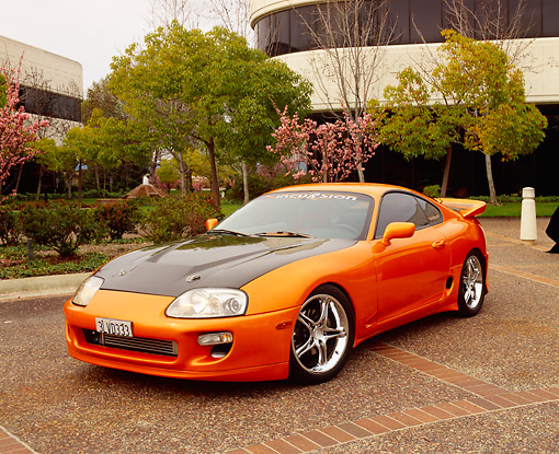 AUT 25 RK1265 02 © Kimball Stock 1995 Toyota Supra Custom Orange And Black 3/4 Front View By Building And Trees