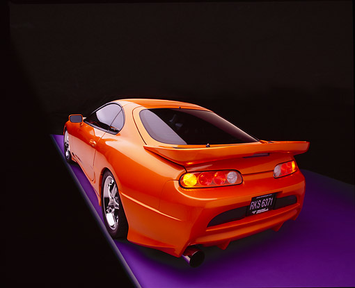 AUT 25 RK1269 09 © Kimball Stock 1995 Toyota Supra Custom Orange And Black Wide Angle Rear 3/4 Rear View On Gray Line Purple Floor Studio
