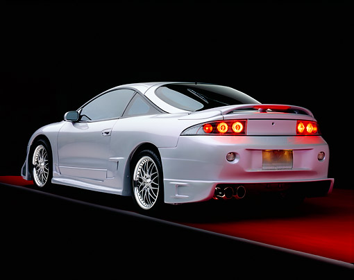 AUT 25 RK1284 01 © Kimball Stock 1998 Mitsubishi Custom Modified Eclipse GS Silver And Black 3/4 Rear View On Red Floor Gray Line Studio
