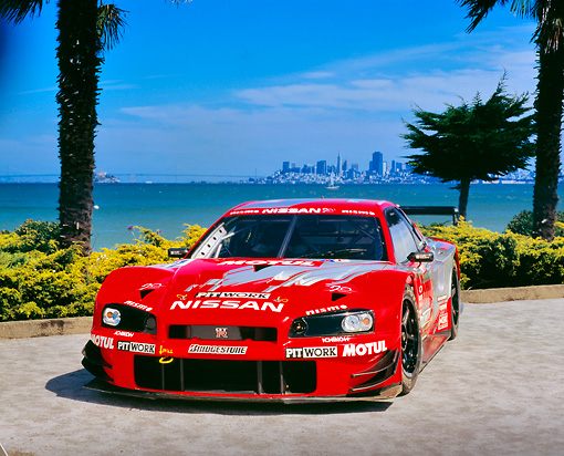 AUT 25 RK1375 02 © Kimball Stock 1999 Nissan Skyline Nismo Race Car Red 3/4 Front View By Water City Background