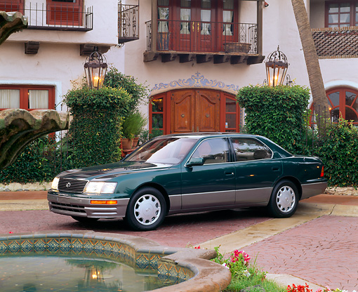 AUT 25 RK0046 02 © Kimball Stock 1996 Lexus LS400 Green 3/4 Side View On Brick Floor By Building