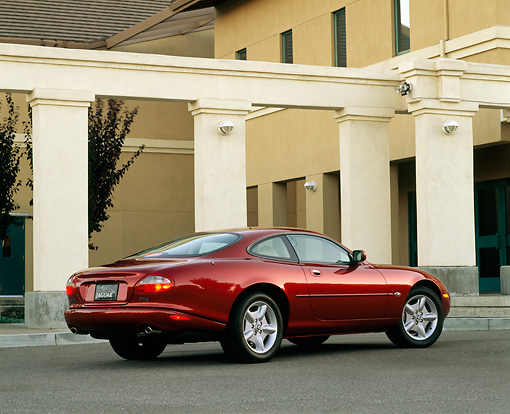 AUT 25 RK0054 02 © Kimball Stock 1997 Jaguar XK8 Burgundy Rear 3/4 View On Pavement By White Pillars