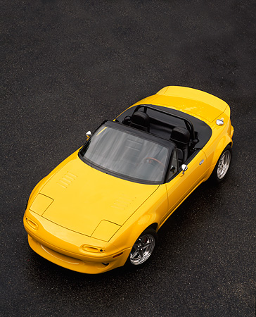 AUT 25 RK0092 01 © Kimball Stock 1997 Mazda Miata V8 Yellow Convertible Overhead 3/4 Front View On Pavement